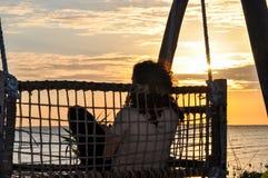 Mujer que se sienta con el fondo de la puesta del sol imágenes de archivo libres de regalías