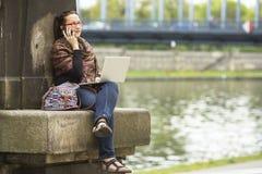 Mujer que se sienta con el ordenador portátil al aire libre en la ciudad y que habla en el teléfono Fotos de archivo libres de regalías