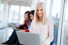 Mujer que se sienta con el ordenador portátil en campus universitario Imágenes de archivo libres de regalías