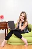 Mujer que se sienta con el ordenador portátil Imagen de archivo libre de regalías
