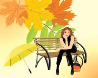 Mujer que se sienta con el paraguas en el banco de madera Imagen de archivo