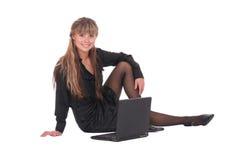 Mujer que se sienta con la computadora portátil Imagen de archivo libre de regalías