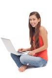 Mujer que se sienta con la computadora portátil Fotografía de archivo