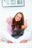 Mujer que se sienta con la computadora portátil que muestra los pulgares para arriba Imagen de archivo libre de regalías