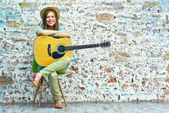 Mujer que se sienta con la guitarra acústica Foto de archivo