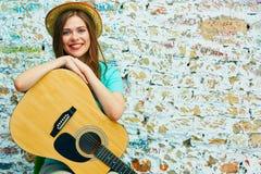 Mujer que se sienta con la guitarra acústica Fotos de archivo