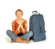 Mujer que se sienta con la maleta en blanco Foto de archivo libre de regalías