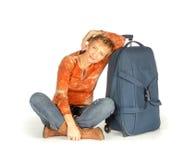 Mujer que se sienta con la maleta en blanco Fotos de archivo libres de regalías