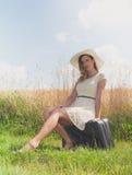 Mujer que se sienta con la maleta en un borde del campo foto de archivo libre de regalías