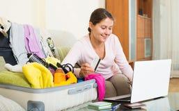 Mujer que se sienta con la tarjeta de crédito cerca del ordenador portátil y del equipaje Imagenes de archivo