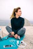 Mujer que se sienta con los accesorios del deporte imagen de archivo libre de regalías