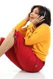 Mujer que se sienta con los auriculares Imágenes de archivo libres de regalías