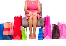 Mujer que se sienta con los bolsos de compras Imágenes de archivo libres de regalías