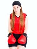Mujer que se sienta con los guantes de boxeo sobre blanco Imagenes de archivo