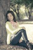 Mujer que se sienta contra un árbol Fotos de archivo libres de regalías