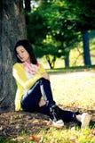 Mujer que se sienta contra un árbol Imagen de archivo