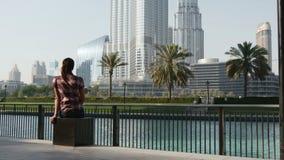 Mujer que se sienta delante de Burj Khalifa almacen de metraje de vídeo