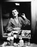Mujer que se sienta delante de su vanidad que mira en el espejo (todas las personas representadas no son vivas más largo y ningún Fotografía de archivo libre de regalías