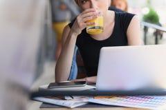 Mujer que se sienta delante de un ordenador portátil Imagen de archivo libre de regalías