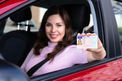 Mujer que se sienta dentro del coche que muestra el carn? de conducir imagenes de archivo