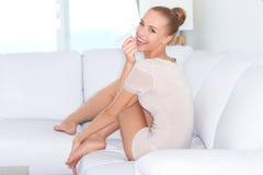 Mujer que se sienta descalzo en un sofá blanco Fotografía de archivo libre de regalías