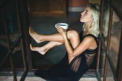 Mujer que se sienta en alféizar con la taza Foto de archivo libre de regalías