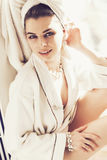 Mujer que se sienta en alféizar en toalla y traje en cuarto de baño Fotografía de archivo