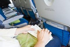 Mujer que se sienta en aviones con los documentos de embarque Imagen de archivo libre de regalías