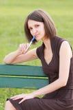 Mujer que se sienta en banco Fotos de archivo