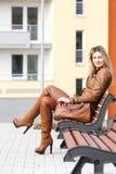 Mujer que se sienta en banco Foto de archivo
