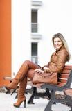 Mujer que se sienta en banco Imagen de archivo libre de regalías