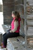 Mujer que se sienta en banco de madera Fotos de archivo
