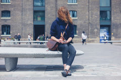 Mujer que se sienta en banco del granito usando el teléfono elegante Foto de archivo