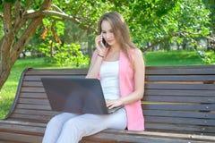 Mujer que se sienta en banco en el parque que habla en el teléfono celular y que usa el ordenador portátil Imagen de archivo