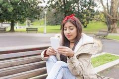 Mujer que se sienta en banco y que mira el messahe su smartphone Imagenes de archivo