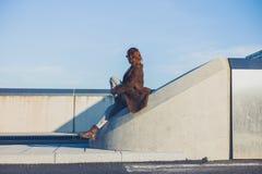 Mujer que se sienta en barrera en el camino Fotos de archivo libres de regalías