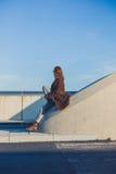 Mujer que se sienta en barrera en el camino Fotografía de archivo