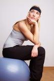 Mujer que se sienta en bola de la gimnasia Imagen de archivo libre de regalías