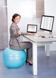 Mujer que se sienta en bola de los pilates usando el ordenador Foto de archivo libre de regalías