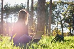 Mujer que se sienta en bosque con el ordenador portátil que goza del sol de la última hora de la tarde Fotos de archivo libres de regalías