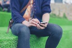 Mujer que se sienta en césped del astro usando el teléfono elegante Fotos de archivo libres de regalías