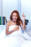 Mujer que se sienta en cama por debajo el edredón y la sonrisa Imagen de archivo