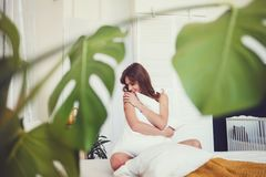 Mujer que se sienta en cama y que abraza la almohada blanca imagen de archivo libre de regalías