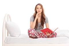 Mujer que se sienta en cama y que sostiene un libro Imagen de archivo