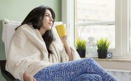 Mujer que se sienta en casa, envuelto en una manta, té de consumición imágenes de archivo libres de regalías