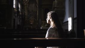 Mujer que se sienta en catedral oscura almacen de metraje de vídeo