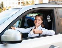 Mujer que se sienta en coche y que muestra los pulgares para arriba Fotografía de archivo