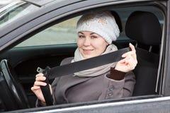 Mujer que se sienta en coche y que sostiene el cinturón de seguridad Imagen de archivo