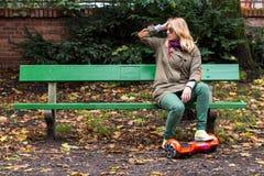 Mujer que se sienta en el banco con hoverboard Foto de archivo