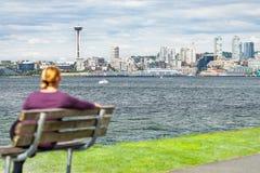 Mujer que se sienta en el banco que mira la Seattle, Washington Skylin fotografía de archivo